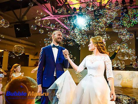 Жених и невеста в свадебном платье на фото среди мыльных пузырей