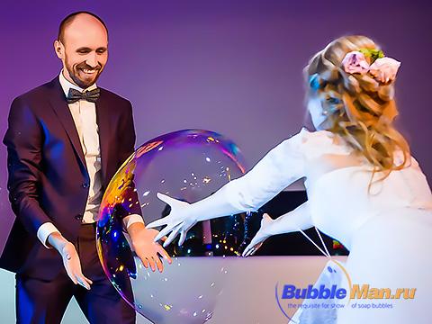 Жених и невеста ловят огромный мыльный пузырь